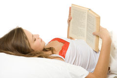 Girl Reading Book In Bed Stock Photo