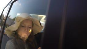 Girl Reading Book Inside Car in backseat. Girl with straw hat Reading Book Inside Car in backseat. road trip concept stock video