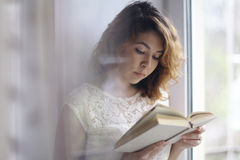 Girl reading a book isolated oriental Stock Photo