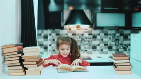 Girl reading a book in the kitchen. Fast play. Timelapse. stock footage