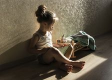 A girl is reading a fairy tale from a book to a cat in a crib Royalty Free Stock Images