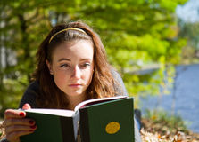 Girl reading book while laying down. Girl reads book for school in fall scene while laying down in the leaves and grass stock photo