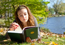 Girl reading book while laying down. Girl reads book for school in fall scene while laying down in the leaves and grass Stock Photos