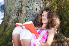 Girl Reading Book While Leaning On Tree Trunk Royalty Free Stock Images