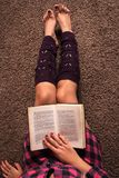 Girl reading book and legs with warmers on carpet floor Stock Photography