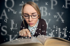 Girl reading a book with letters coming out of the book Royalty Free Stock Photography