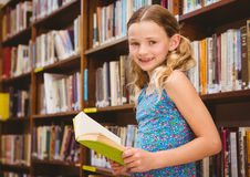 Girl reading book in library Royalty Free Stock Photo