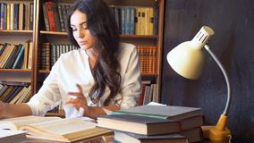 Girl reading a book in the library is preparing for the exam stock footage