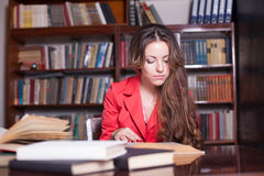 Girl reading book in the library is preparing for exams Stock Photography