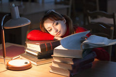 Girl reading a book in the library under the lamp Royalty Free Stock Photography