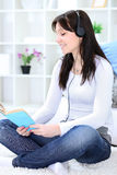 Girl reading book and listening music Royalty Free Stock Photography