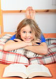 Girl reading a book. Little kid - lying girl reading a book on bed Royalty Free Stock Images