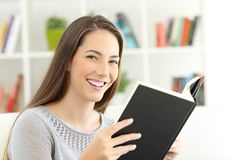 Girl reading a book and looking at camera Stock Images