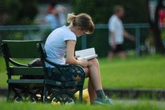 Girl reading a book. At lumphini park in Thailand royalty free stock photography