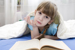 Girl reading a book lying in bed Royalty Free Stock Images
