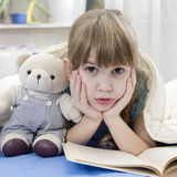 Girl reading a book lying in bed with teddy-bear Stock Image