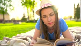 Girl reading book lying down on a blanket in the park at sunset. Traditional reading stock footage