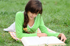 Girl reading a book lying on grass Stock Photo
