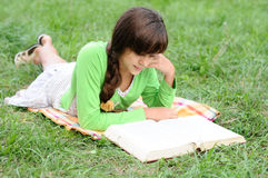 Girl reading a book lying on grass Royalty Free Stock Photo