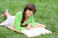 Girl reading a book lying on grass Royalty Free Stock Image