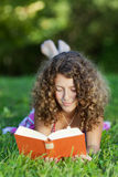 Girl Reading Book While Lying On Grass Royalty Free Stock Images
