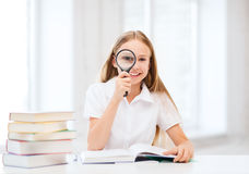 Girl reading book with magnifier at school Stock Photography