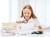 Girl reading book with magnifier at school Royalty Free Stock Photos