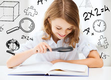 Girl reading book with magnifier at school Royalty Free Stock Photography