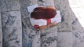 Girl reading a book on marble stairs, high-angle shot, Italy stock video footage