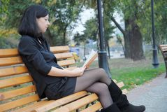 Girl reading a book on the nature Royalty Free Stock Image