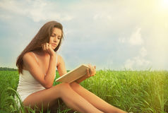 Girl reading a book on nature. Beautiful girl student reading a book on the lawn in the park Royalty Free Stock Photo