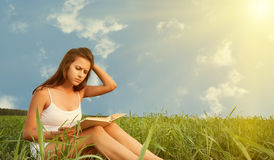 Girl reading a book on nature Royalty Free Stock Photography