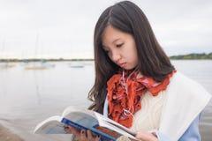 Girl reading book near lake Stock Photos