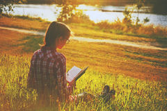 Girl reading book near river Royalty Free Stock Image