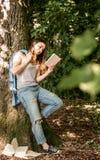 Girl reading a book near a tree Stock Photography