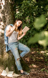 Girl reading a book near a tree Royalty Free Stock Image