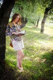 A girl is reading a book near a tree. A girl is standing by a tree in a summer park and reading a book Royalty Free Stock Images