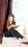 Girl reading book near the window Stock Photography