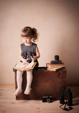 Girl reading a book on the old suitcase Stock Photography