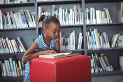Girl reading book on ottoman in library. Girl reading book on ottoman against bookshelf in library Royalty Free Stock Photos