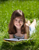 Girl reading book outdoor. Girl reading book lying on green meadow Stock Photo