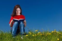 Girl reading book outdoor. Girl reading book sitting on green meadow Stock Photography