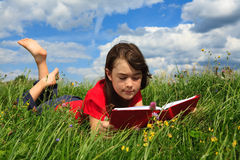 Girl reading book outdoor. Girl reading book on green meadow Royalty Free Stock Image