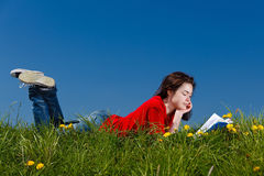 Girl reading book outdoor. Girl reading book lying on green meadow Royalty Free Stock Images
