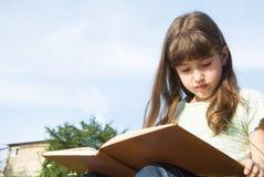 Girl reading a book, outdoor scene Stock Photo