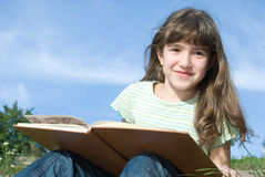 Girl reading a book, outdoor scene Royalty Free Stock Photography