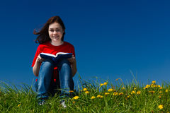 Girl reading book outdoor Stock Image