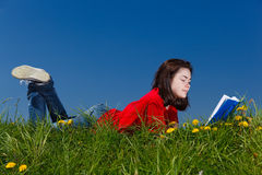 Girl reading book outdoor. Girl reading book sitting on green meadow Stock Images