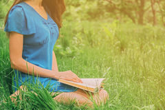 Girl reading book outdoor in summer Royalty Free Stock Photo