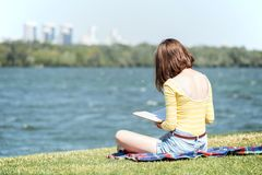 Girl reading a book. At the outdoors stock photography